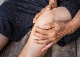 Image of a person holding knee with Osteoarthritis