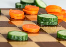 Chessboard with carrots and cucumber
